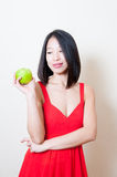 Young beautiful asian woman red dress looking green apple Stock Image