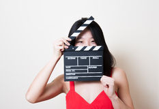 Young beautiful asian woman red dress smiling eyes with clapperb Royalty Free Stock Photography