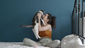 Girl and her little funny kitty together. Young beautiful Asian woman relaxing and playing with her lovely cat on bed in