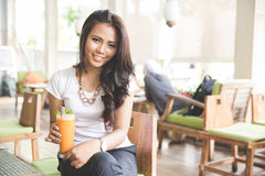 Young beautiful asian woman in a restaurant, enjoying her drink Stock Images