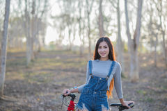 Young and beautiful asian woman riding bicycle outdoors in park Royalty Free Stock Images