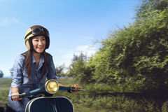 Young beautiful asian woman riding his scooter Stock Images