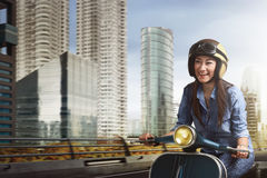 Young beautiful asian woman riding scooter amid the city. With very happy Royalty Free Stock Photos