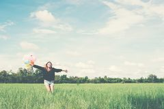 young beautiful asian woman running and jumping on green grassland with colored balloons enjoy fresh air royalty free stock images