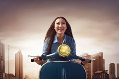 Young beautiful asian woman sitting on a blue scooter. On the city Royalty Free Stock Image