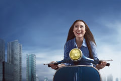 Young beautiful asian woman sitting on a blue scooter during the Royalty Free Stock Photo