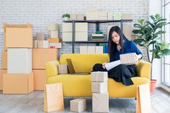 Young and beautiful Asian woman sitting among several boxes and royalty free stock photos