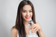 Young beautiful Asian woman with smiley face and red lips holdin. G water bottle Royalty Free Stock Photos