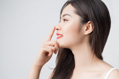 Young beautiful Asian woman with smiley face and red lips touch Royalty Free Stock Photography
