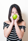 Young beautiful asian woman smiling with green apple over mouth Royalty Free Stock Photo