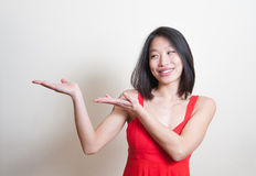 Young beautiful asian woman smiling pointing out white backgroun Stock Photography