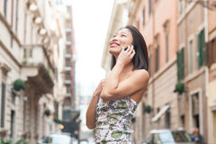 Young asian woman smiling with mobile phone urban outdoor Stock Image