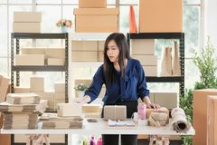 Young and beautiful Asian woman standing among several boxes and stock images