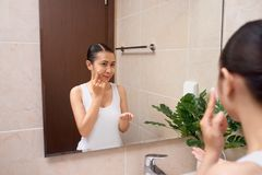 Young beautiful asian woman washing her face with hands by soap Stock Photos