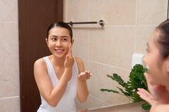 Young beautiful asian woman washing her face with hands by soap Royalty Free Stock Photo