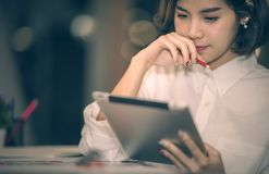 Young woman holding pencil touch the lips. Young beautiful asian woman in white shirt holding pencil touch the lips while looking at tablet Stock Photos
