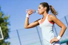 Young beautiful athlete drinking water after exercising Royalty Free Stock Image