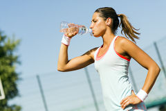 Young beautiful athlete drinking water after exercising Stock Image