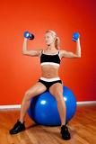 Young beautiful athlete sitting on fitness ball. Beautiful blond athlete sitting on fitness ball with dumbbells Stock Images