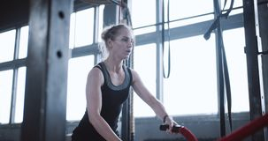 Young beautiful athletic blonde Caucasian woman working out with battle ropes and resting in large gym slow motion. Motivation and determination, female stock footage