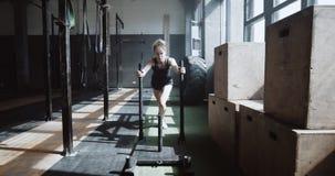 Young beautiful athletic Caucasian woman pushing training sled towards camera, exercising in hardcore gym slow motion. Professional female athlete doing power stock video footage