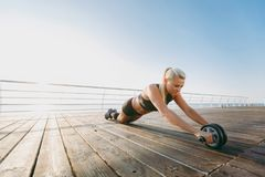 Young beautiful athletic girl with long blond hair in black clothes training with dumbbells at sunrise over the sea Royalty Free Stock Image