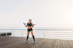 Young beautiful athletic girl with long blond hair in headphones, listening to music and training with dumbbells at sunrise over t Stock Photos