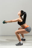 Young, beautiful, athletic girl performs squats Royalty Free Stock Images