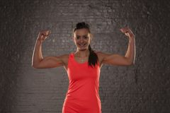 Young beautiful athletic girl shows her biceps royalty free stock images