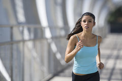 Young beautiful athletic sport woman running and jogging crossing modern metal city bridge stock photography