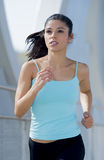 Young beautiful athletic sport woman running and jogging crossing modern metal city bridge Royalty Free Stock Photo
