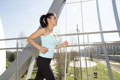Young beautiful athletic sport woman running and jogging crossing modern metal city bridge Stock Photos