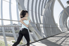 Young beautiful athletic sport woman running and jogging crossing modern metal city bridge Stock Photo