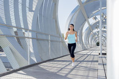 Young beautiful athletic sport woman running and jogging crossing modern metal city bridge Royalty Free Stock Images