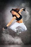 Young beautiful athletic woman dancing modern dance hip-hop. On wall background with smoke royalty free stock images
