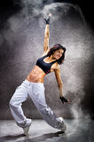 Young beautiful athletic woman dancing modern dance hip-hop. On wall background with smoke stock photos