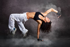 Young beautiful athletic woman dancing modern dance hip-hop. On wall background with smoke royalty free stock photography