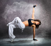 Young beautiful athletic woman dancing modern dance hip-hop. On wall background with smoke royalty free stock photos