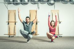 Young beautiful and attractive fitness couple workout on their balance by standing on the one leg in yoga position exercise royalty free stock photography