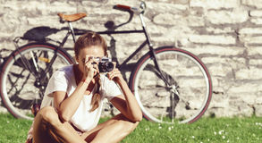 Young, beautiful attractive hipster girl taking pictures in park Stock Photo