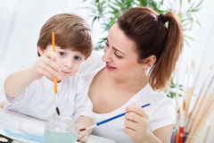 Young beautiful attractive mother learn her child how to paint Stock Photos