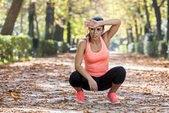 Attractive sport woman in runner sportswear breathing gasping and taking a break tired and exhausted after running workout on Autu. Young beautiful and Stock Photo