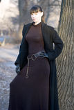 Young beautiful attractive woman in dress and coat. Young beautiful attractive woman wearing a long dress and warm coat during the cold winter season standing Stock Photo
