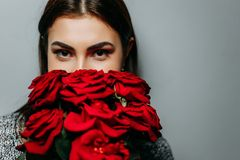Young beautiful attractive woman hiding behind red roses. Girl w. Ith flowers. Valentine day, romantic concept Royalty Free Stock Image