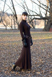 Young beautiful attractive woman in long dress. Young beautiful attractive woman wearing a long dress during winter season standing outside in the park Stock Photos
