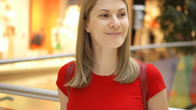 Young beautiful attractive woman standing in shopping mall, smiling. Shopping consumerism concept. Young beautiful attractive woman in red t-shirt standing in stock video