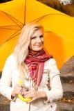 Young beautiful autumn woman with yellow umbrella Stock Photos