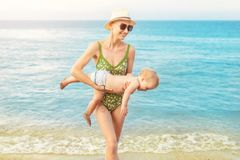 Young beautiful bald mother carrying cute caucasian toddler boy out clear blue water at tropical beach with warm summer rain. Mom stock image