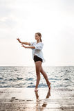 Young beautiful ballerina dancing and posing outside, sea background. Stock Photo