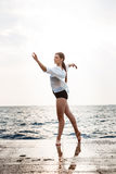 Young beautiful ballerina dancing and posing outside, sea background. Royalty Free Stock Image